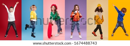 Set of playful multiethnic kids in stylish casual clothes having fun while standing against bright background in studio