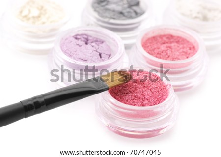 Set of powder eye shadows in jars and brush on white background.