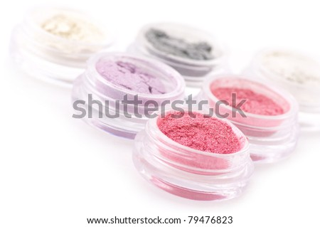 Set of powder eye shadows in jars on white background.