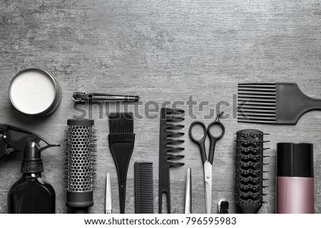 Set of professional hairdresser tools on light grey background