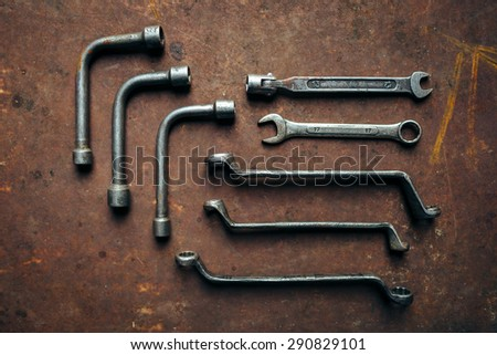 Set of professional wrenches on a rusty dark metal background