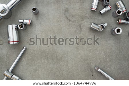 Set of Ratchets wrench and socket placed on concrete texture background with space for text in the middle