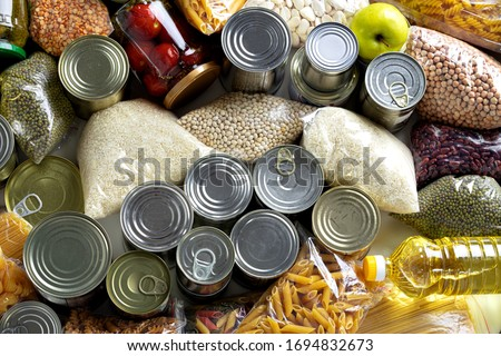 Set of raw cereals, grains, pasta and canned food on the table.