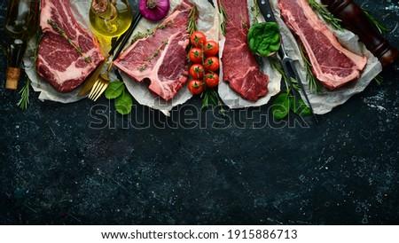 Set of raw steaks - t-bone, tomahawk, striploin, tenderloin, new york steak. On a black stone background. Top view.
