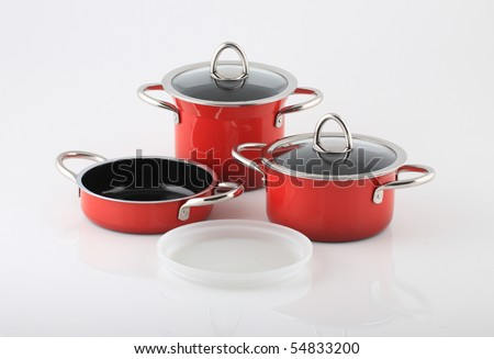 Set of red pots and pans on white background.