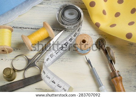 Set of reel of thread, centimeter, fabric, thimble and scissors, seam ripper and toothed wheel for sewing and needlework on the wooden board in Shabby Chic style.