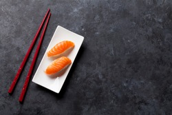 Set of salmon nigiri sushi and chopsticks on stone table. Top view with copy space