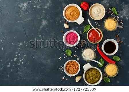 Set of sauces in bowls - ketchup, mayonnaise, mustard, soy sauce, bbq sauce, pesto, chimichurri, mustard grains on dark stone background. Top view copy space. Foto stock ©