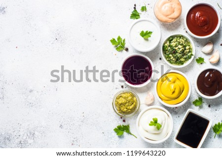 Set of sauces - ketchup, mayonnaise, mustard soy sauce, bbq sauce, pesto, chimichurri, mustard grains and pomegranate sauce on white background.