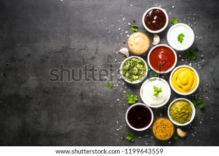 Set of sauces - ketchup, mayonnaise, mustard soy sauce, bbq sauce, pesto, chimichurri, mustard grains and pomegranate sauce on dark stone background. Top view copy space.