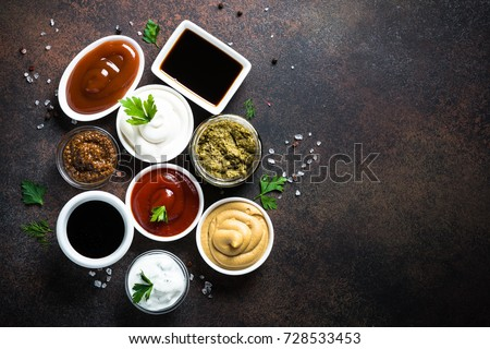 Set of sauces - ketchup, mayonnaise, mustard soy sauce, bbq sauce, pesto, mustard grains and pomegranate sauce on dark rusty stone or metal background. Top view copy space. #728533453