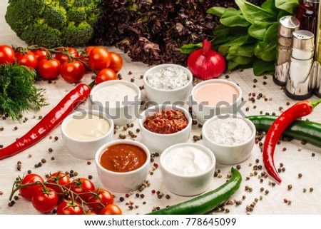 Set of sauces - ketchup, mayonnaise, mustard soy sauce, bbq sauce, pesto, mustard grains and pomegranate sauce on white wooden background. Top view. #778645099