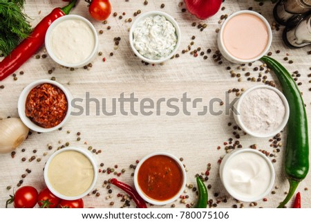 Set of sauces - ketchup, mayonnaise, mustard soy sauce, bbq sauce, pesto, mustard grains and pomegranate sauce on white wooden background. Top view. #780075106