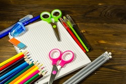 Set of school stationery supplies. Blank notebook, colored pencils, pens, scissors, eraser on wooden desk. Back to school concept