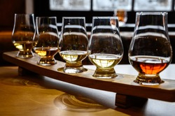 Set of Scottish whisky, tasting glasses with variety of single malts or blended whiskey spirits on distillery tour in Scotland, UK