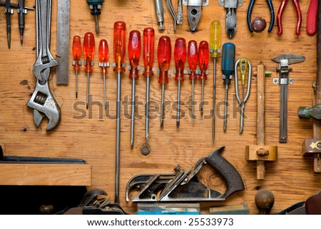 set of screwdrivers and other tools hanging in wooden cupboard against a wall