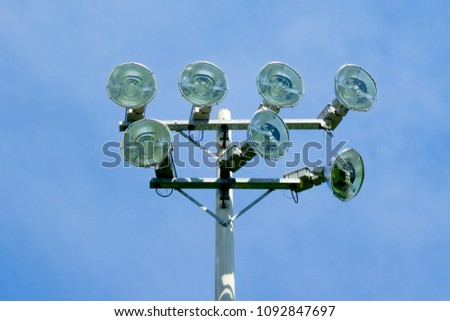 Set of seven powerful stadium floodlights on tower against blue sky. #1092847697