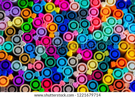 Set of several colored markers of different colors, the top view of the covers. Abstract colorful background from multi-colored caps for plastic pens #1221679714