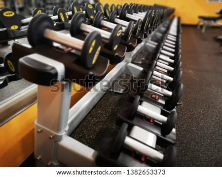 Set of several dumbbells on gym dumbbell rack