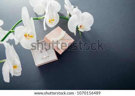 Set of silver ring and earrings with pearls in the gift box with white orchid. Present for a Mother's Day with flowers