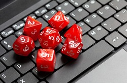 Set of simple red RPG role playing fantasy board game dice laying on a modern laptop computer keyboard, closeup, from above, nobody. Online rpg pc games, roleplay, nerd culture abstract concept