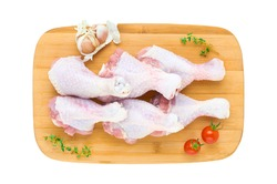 Set of six fresh chicken drumsticks on a wooden cutting Board with vegetables and herbs isolated on a white background. The view from the top.