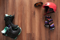 set of snowboard equipment  boots, helmet, gloves and mask on a wooden floor with copyspace