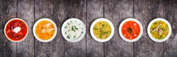 Set of soups from worldwide cuisines, healthy food. Cream soup with mushrooms, asian fish soup, soup with meat - solyanka, russian borscht, chicken soup on rustic wooden background. Top view