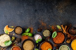 Set of Spices and herbs for cooking. Small bowls with colorful  seasonings and spices - basil, pepper, saffron, salt, paprika, turmeric. On black stone table top view copy space