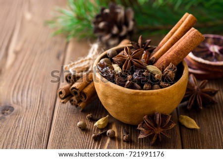 Set of spices for mulled wine in ceramic bowl on wooden table. Cinnamon sticks, star anise, cardamom, cloves, allspice and raisins. Selective focus. #721991176
