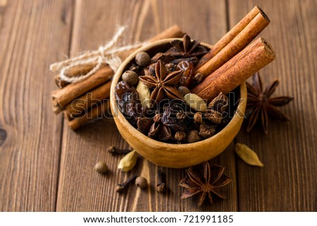 Set of spices for mulled wine in ceramic bowl on wooden table. Cinnamon sticks, star anise, cardamom, cloves, allspice and raisins. Selective focus. #721991185