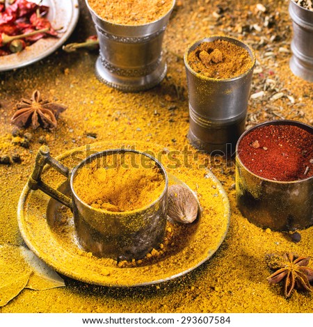 Set of spices pepper, turmeric, anise, coriander in vintage metal cups over yellow curry powder. Square image with selective focus.