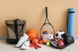 Set of sport equipment on floor near color wall