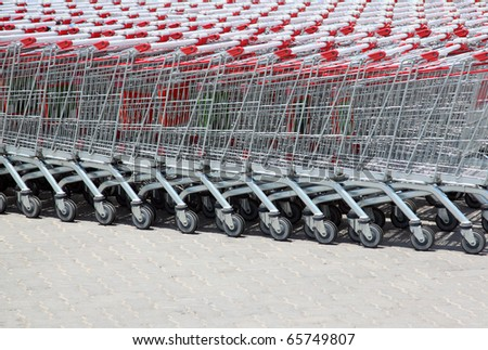 Set of stacked supermarket trolleys with red handle out of doors