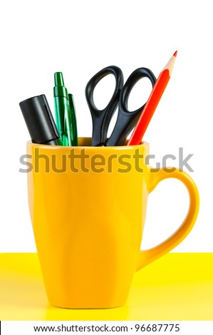 Set of stationery kit in bright yellow cup.