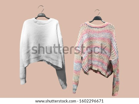 Set of striped female knit sweater with long sleeves and white flecked sweater on a hanger isolated on pink background. Autumn and winter clothes. Composition of clothes. Winter clothes pattern
