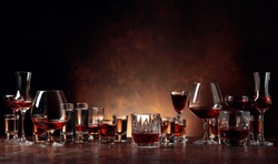 Set of strong alcoholic beverages in glasses on a brown background. In the presence of liquor, whiskey, vodka, rum, brandy, tequila.