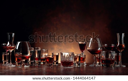 Set of strong alcoholic beverages in glasses on a brown background. In the presence of liquor, whiskey, vodka, rum, brandy, tequila.  #1444064147