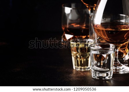 Set of strong alcoholic drinks in glasses and shot glass in assortent: vodka, rum, cognac, tequila, brandy and whiskey. Dark vintage background, selective focus #1209050536