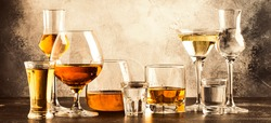 Set of strong alcoholic drinks in glasses in assortment: vodka, cognac, tequila, brandy and whiskey, grappa, liqueur, vermouth, tincture, rum. Panoramic banner with copy space