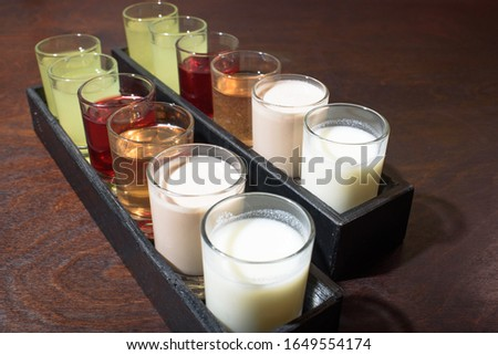 Set of strong and not strong tinctures on a wooden table. Alcoholic drinks. Harmful drinks.