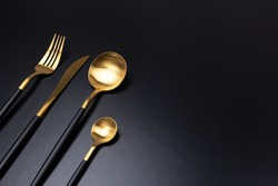 Set of stylish black and gold cutlery on black background. Dark and moody vibes. Fashionable and luxury eating. Flat-lay, top view. Copy space for your text.