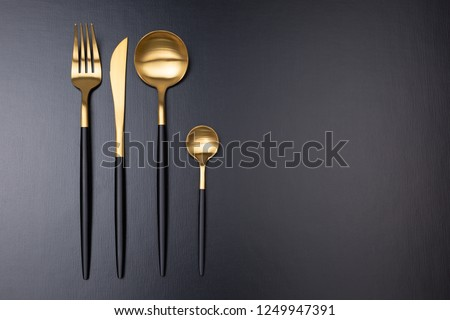 Set of stylish black and gold cutlery on black background. Dark and moody vibes. Fashionable and luxury eating. Flat-lay, top view. Copy space for your text. Photo stock ©