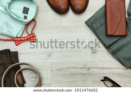 Set of stylish male hipster clothes on wooden background #1011476602