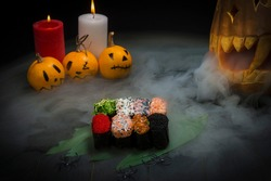 Set of Sushi Gunkan served in Halloween party style with pumpkin lantern exhaling smoke. Horror serving food concept. Funny painted pumpkins on dark background near burning candles. Variety of sushi