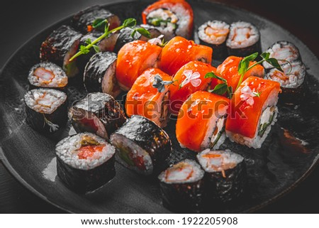 set of sushi roll with salmon, avocado, cream cheese, cucumber, rice, tuna in plate on black background