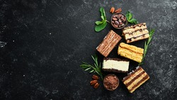 Set of sweet pieces of cakes and sweets on a black stone background. Top view.