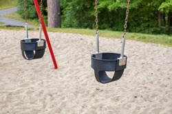 Set of  swings on chains for little children in the park with sand underneath and trees in the background