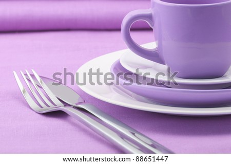 Set of tableware on lilac tablecloth.