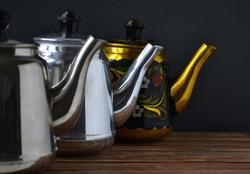 Set of teapots on dark background. Metal teapots in a row.